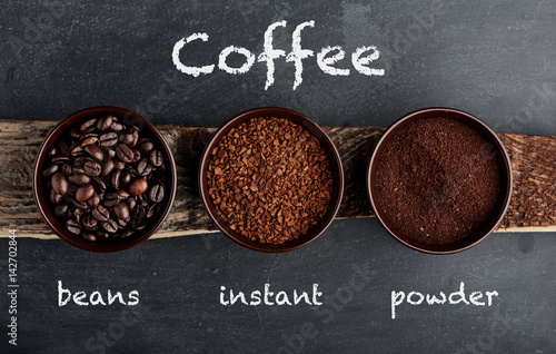 Three types of coffee in cups on wooden plank with inscription.