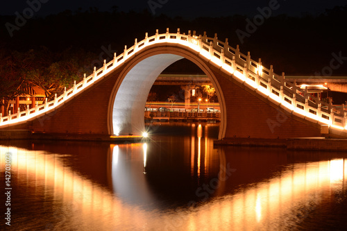 Traditional Chinese bridge and reflection over Dahu Park lake at night in Taipei, Taiwan