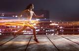Läuferin joggt vor beleuchteter Stadt - 142712433