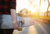 Rear view of skateboard girl holding skateboard