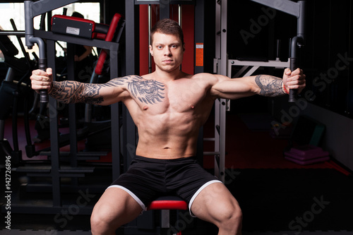 Athletic man with naked torso performing crossover exercise for chest muscles at Poster