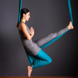 young beautiful brunette woman doing fly yoga. Sitting in hammock with namaste gesture. Wellness concept.