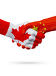 Flags Canada, China countries, partnership friendship handshake concept.