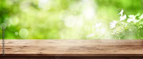 Leinwandbild Motiv Radiant green spring background with wooden table