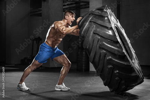 Muscular man working out in gym flipping tire, strong male naked torso abs
