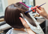 Fototapety The hairdresser paints the woman's hair in a dark color, apply the paint to her hair in the beauty salon.