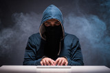 Computer hacker working in dark room - 142854248