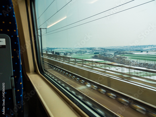 View outside of 300km/h bullet train passing snow covered crops in Louyang, Chin Poster