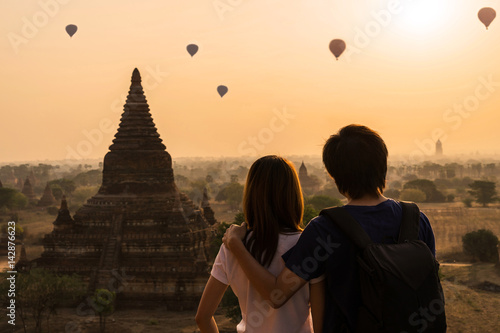Poster Couple traveler looking at balloons over ancient pagoda