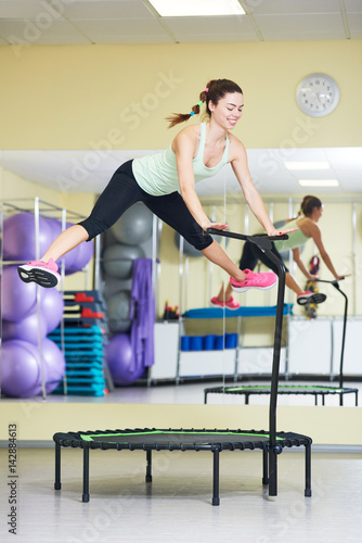 Fitness activity. Woman jumping on trampoline