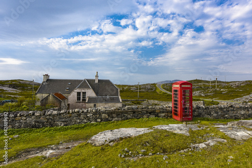 Red telephone box near an old building on Harris Islands Poster