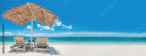 Two chairs and umbrella on beach - 142915634