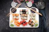 Japanese cuisine. Sushi set on a white plate over dark stone background.