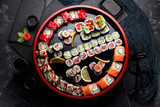 Japanese cuisine. Asian food. Sushi set on a wooden round plate. Stone background.