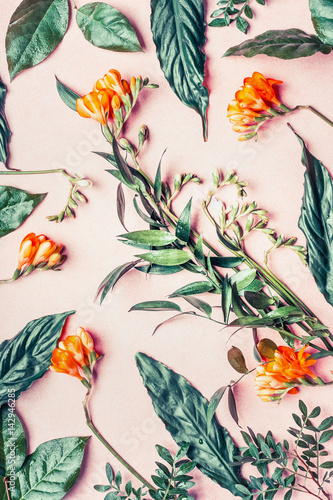 Creative flat lay made of tropical flowers and leaves on pastel pink background, top view