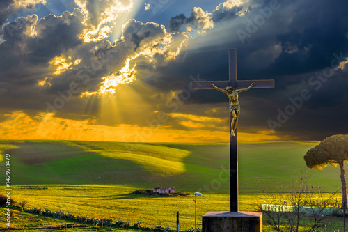 Jesus Christ on the cross by the road in the fields at sunset, with drammatic clouds and sun rays on the sky Poster
