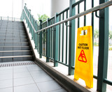Wet floor caution sign near the stairs. - 142980238
