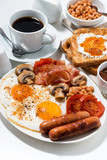 Fototapety English breakfast of scrambled eggs with bacon, sausages and vegetables, vertical
