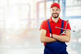 Fototapeta car repair service - smiling auto mechanic with wrench in hand