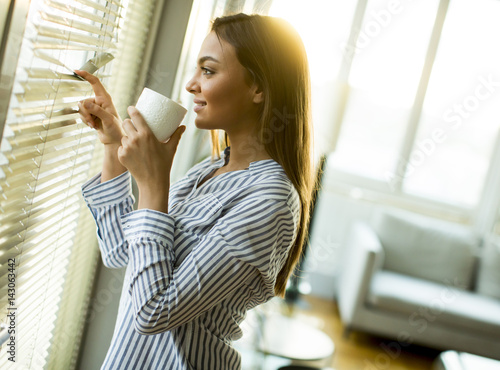 Attractive  young woman holding cup with hot tea or coffee and looking at the sunrise standing near the window in room - 143063442