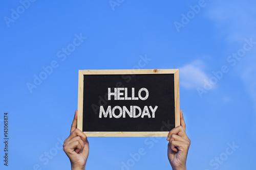 HELLO MONDAY/ Man holding small blackboard on blue sky background.