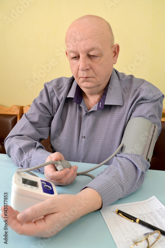 The elderly man measures pressure by an electronic tonometer semiautomatic devic Poster