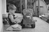 Young boy playing with his plastic truck toy