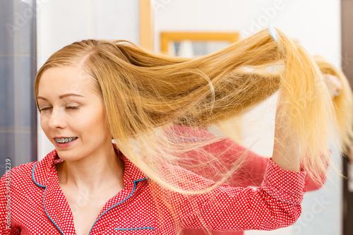 Woman combing her long hair in bathroom © Voyagerix