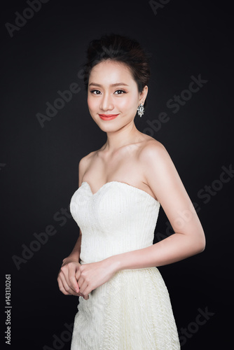 Plakat Fashion portrait of beautiful young asian woman in white dress over dark background