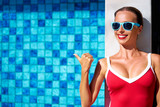 Happy vacation. Showing advertising. Pretty young woman in red swimsuit pointing copy space at swimming pool. - 143130839