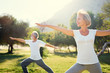 Leinwanddruck Bild - Yoga at park. Senior family couple exercising outdoors. Concept of healthy lifestyle.