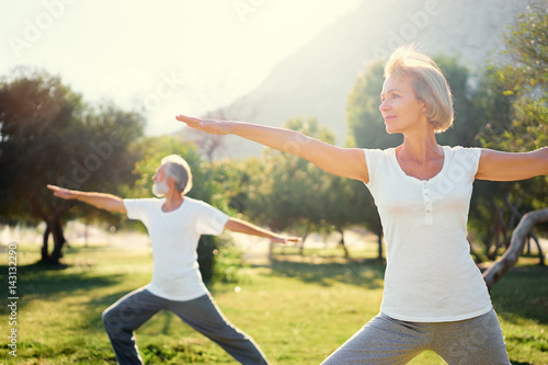 Leinwanddruck Bild Yoga at park. Senior family couple exercising outdoors. Concept of healthy lifestyle.