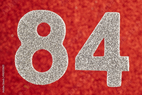Poster Number eighty-four silver color over a red background