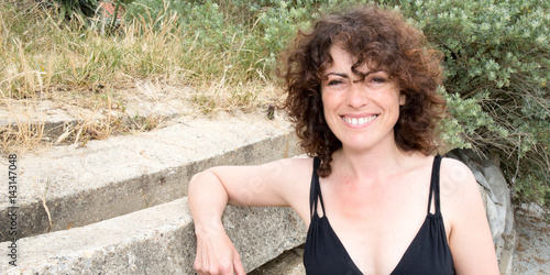 middle-aged woman with curly hair tourists during the summer holidays Poster