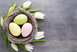 Fototapeta Easter eggs in the nest on a gray background. Spring greeting card.