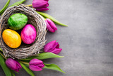 Fototapeta Spring greeting card. Easter eggs in the nest. Spring flowers tulips.