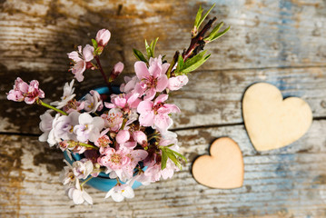 Shabby chic wedding background with spring blossom an wooden hearts on old wood background