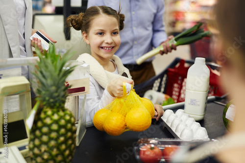 Happy girl giving oranges to cashier at supermarket checkout
