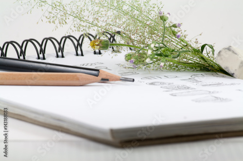 Flowers, pencil, book and a notebook  isolated on white background