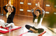 Cute girls on a yoga class.  Two beautiful teenage girls enjoying on a yoga training in a gym. camera and smiling. Indoors.