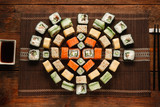 Japanese delicious and fresh set of colorful sushi rolls served on brown straw mat, flat lay. Food art, beautiful ornament, luxury restaurant menu photo.