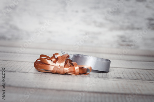 The silver and gold coil of ribbons on a wooden table Poster