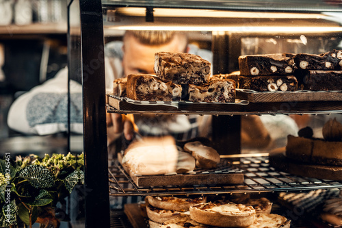 A man holds chocolate cake at the counter in the bakery shop.