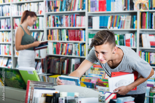Positive teenager boy looking for new book on shelves