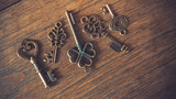 Antique skeleton padlock and retro lock keys on wooden texture background.