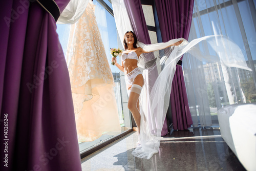 Poster Beautiful bride with flowers in white lingerie showing sexy pose standing at window and dress over her bedroom