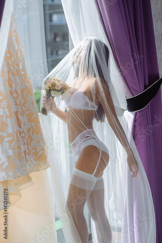 Plakát Beautiful bride with flowers in white lingerie showing sexy pose standing at window and dress over her bedroom
