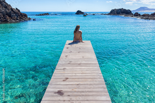 Papiers peints Iles Canaries Spain, Canary Islands, Fuerteventura, Isla de lobos. Topless girl on a pier clear transparent water