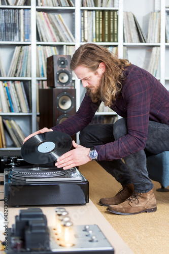 Poster long haired man putting an lp record on the turntable
