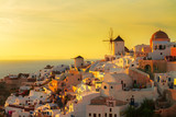 famouse soft orange sunset of Oia with windmill, Santorini island